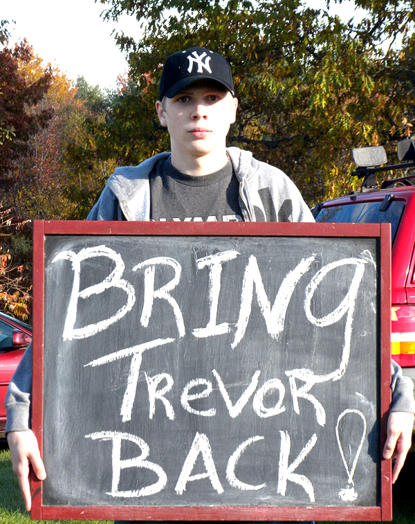 At the Hermon home of one of his supporters Wednesday afternoon, Trevor Moore holds up a sign to advertise his plight.  Moore, 17, said he was expelled from Hermon High earlier this week for a rap song he authored. (Bangor Daily News/Dawn Gagnon)