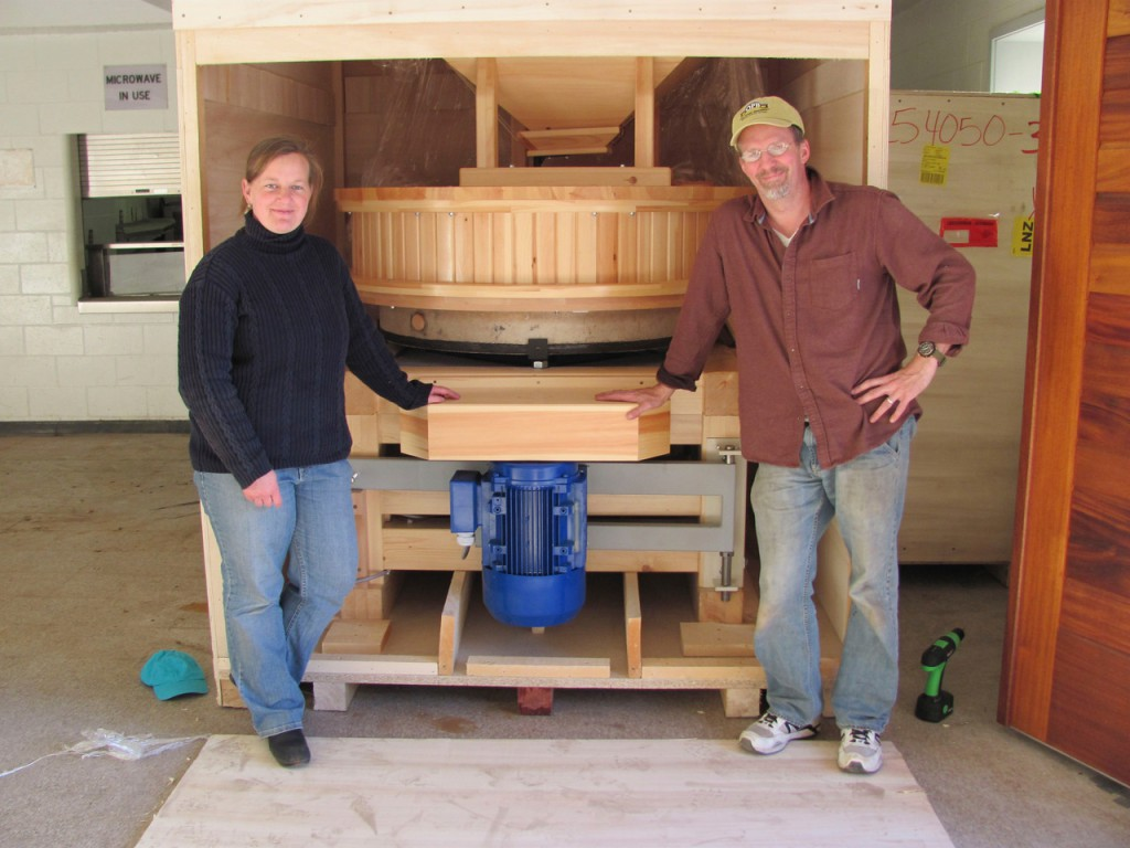 Amber Lambke and Michael Scholz pose with the grist mill they received Tuesday, Oct. 19, 2010, which they intend to put to work in the former Somerset County Jail in downtown Skowhegan. They purchased the building last year. (Bangor Daily News/Christopher Cousins)