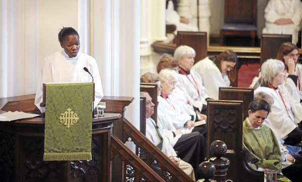 Margarette Saintilver of Haiti (left) preaches at the St. John Episcopal Church in Bangor Sunday morning.  (Bangor Daily News/Gabor Degre)