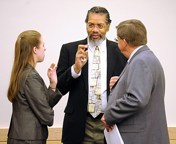 Rory Holland (center) of Biddeford speaks with his attorneys Amanda Doherty (left) and Clifford Strike on the first day of his trial at the Penobscot Juditial Center in Bangor Monday.  Holland is accused of the killing of Dereck Green, 21, and his brother Gage Geen, 19, in Biddeford on June 30th 2009.  (Bangor Daily News/Gabor Degre)