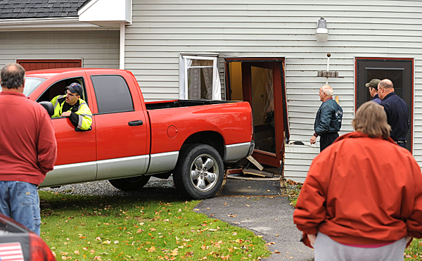 Spectators watch as a wrecker driver moves a Dodge Ram 1500 Hemi away from a building that was struck when Corliss Holland, 87 drove in to the building  while picking up his friend Winifred Reynolds, 81, on Monday, October 25, 2010 at the Hilltop Birches complex on School Street in Belfast.