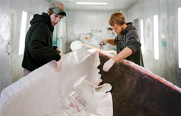 Washington Academy seniors Aaron Farris (left), 17, and Trevor Jessiman, 18, work on an 89-foot dinghy for Jessiman's father in th eir boat-building class Monday. Forty upperclass members are enrolled in the course, which offers students a chance to build boats for three periods a day and learn related skills of navigation and seamanship. (BANGOR DAILY NEWS PHOTO BY BRIDGET BROWN)