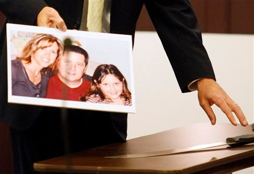 Assistant Attorney General Peter Hinckley displays a photograph of the Cates family while reaching for a machette allegedly used to kill Kimberly Cates and severely injure her daughter, during the first day of Steven Spader's trial Hillsborough Superior Court Tuesday, October 26, 2010. (AP Photo/Bob Hammerstrom, Pool)
