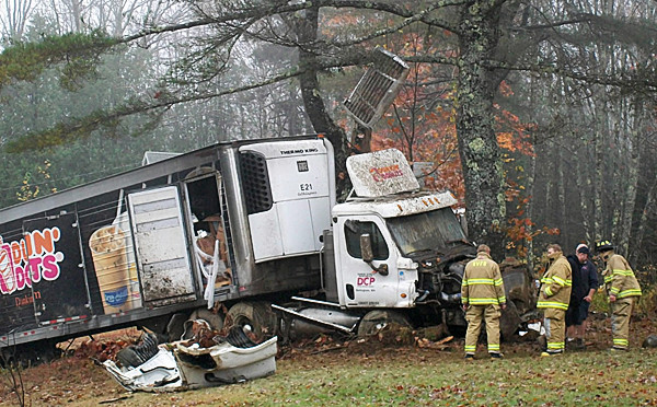 When a car, then a pickup truck, both hit a Dunkin' Donuts tractor trailer on Route 1 in Northport Thursday morning, Oct. 28, 2010, it stripped the large truck of some of its tires.  The driver then lost control of the tractor-trailer, which hit a ditch, went airborne and flew into a large pine tree. All three vehicles involved were totaled and none of the people involved were injured.  BANGOR DAILY NEWS PHOTO BY HEATHER STEEVES