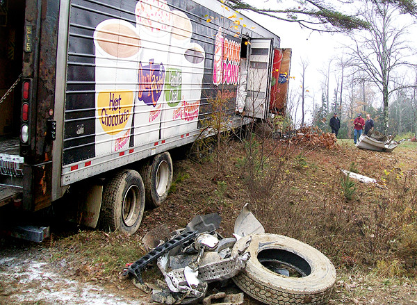 When a car, then pickup truck, both hit a Dunkin' Donuts tractor trailer on Route 1 in Northport Thursday morning, Oct. 28, 2010, it stripped the large truck of some of its tires.  The driver then lost control of the tractor-trailer, which hit a ditch, went airborne and flew into a large pine tree. All three vehicles involved were totaled and none of the people involved were injured.  BANGOR DAILY NEWS PHOTO BY HEATHER STEEVES