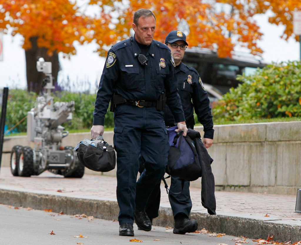 A Portland policeman carries a knapsack, in his left hand, found in the bushes at the federal courthouse, Friday, Oct. 29, 2010, in Portland, Maine. The police bomb squad used a bomb-sniffing dog and a robot to probe the item before the contents of the knapsack were determined harmless. (AP Photo/Robert F. Bukaty)
