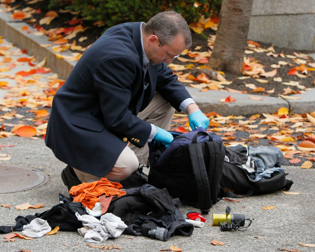 An investigator looks through a knapsack found in the bushes next to the entrance to the federal courthouse, Friday, Oct. 29, 2010, in Portland, Maine. The police bomb squad used a bomb-sniffing dog and a robot to probe the item before the contents of a knapsack were determined harmless. (AP Photo/Robert F. Bukaty)