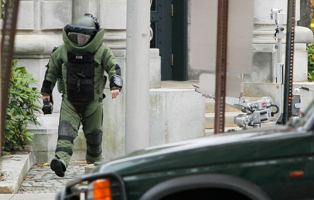 A member of the Portland Police bomb squad carries a camera as he prepares to check a knapsack found in the bushes next to the entrance to the federal courthouse, Friday, Oct. 29, 2010, in Portland, Maine. The police bomb squad used a bomb-sniffing dog and a robot to probe the item before the contents of a knapsack were determined harmless. (AP Photo/Robert F. Bukaty)