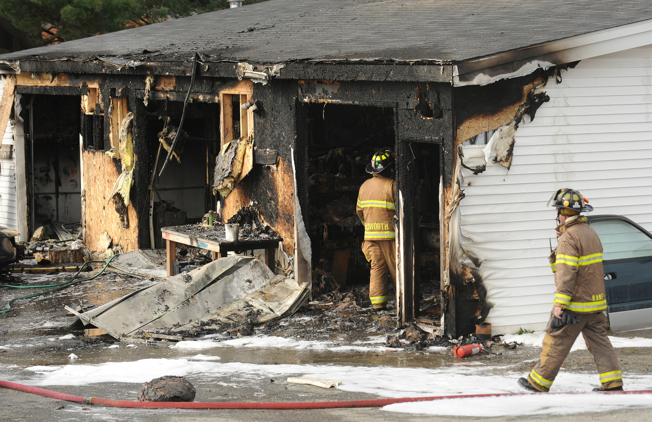 Firefighters look at the damaged building at Jim's Auto Repair shop in Ellworth after they put out the fire Friday afternoon. (Bangor Daily News/Gabor Degre)