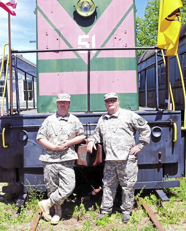 BELFAST - Maine Militia State Commander Mack Page, right, stands next to his son in full uniform in front of one of Page's train cars at his rail yard in Belfast. &quotThe people in the militia have earned the right to wear uniforms,&quot Page said. &quotWe have so many veterans and so many ex-military - this is a way of serving the community.&quot (Photo courtesy of the Maine Militia)