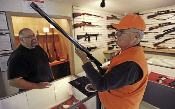 Frank Phinney, right, of Brewer looks over a Marlin Model 94 hunting rifle at The Hunting Lodge on Thursday, October 28, 2010 as shop owner Todd Rogers, left, looks on. Rogers opened the hunting supply store on Route 1A in Holden on October 15. (Bangor Daily News/Kevin Bennett)