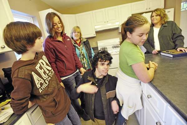 From right: Tommy Brangwynne, 13, Courtney Brangwynne, 23, mother Linda Brangwynne, Andrew Brangwynne, 21, Olivia Brangwynne,10, and Habitat for Humanity of Greater Bangor operating manager Amanda Charette gathered in the family's new kitchen while giving the local media a tour of the Brangwynne family's new home Friday afternoon, Oct. 29, 2010. (Bangor Daily News/John Clarke Russ)