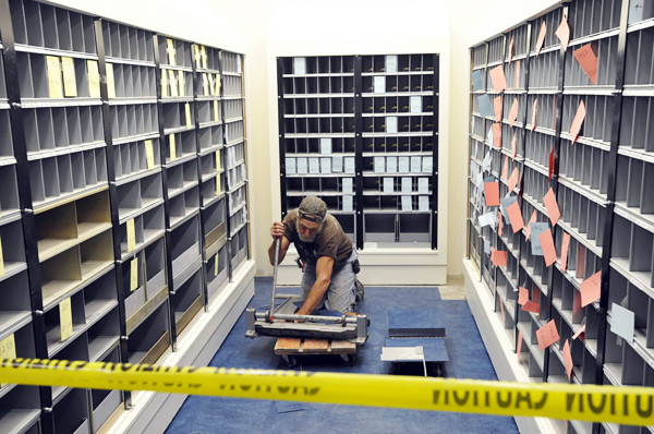 Gary Ballard, an employee of Waterville-based Grenier's Classic Flooring and Design, Inc., cuts fllor tiles in  post office box area of the soon-to-open Bangor post office.The new post office, at the corner of Hammond and Franklin Streets, is set to open Monday, November 1. The interim post office at the Broadway Shopping Center is set to close at 1 p.m Saturday, Oct. 30 to accomodate the weekend move to the new site. (Bangor Daily News/John Clarke Russ)