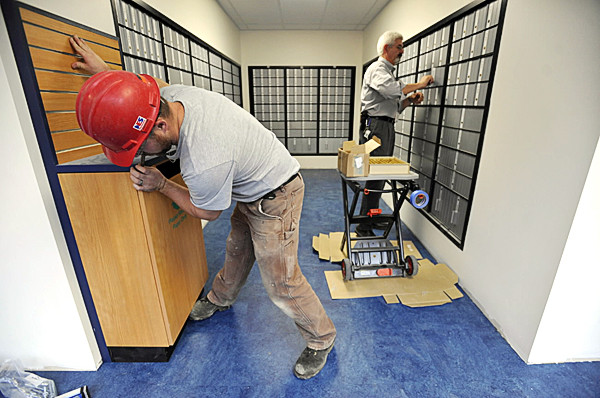 GETTING READY FOR MAIL CALL   Mark Hanscom (right), a post office activation coordinator with the United States Postal Service's Southern Maine Processing and Distribution Center in Scarborough, checks the individual keys in each of more than 1,935 post office box locks Wednesday at Bangor's new post office at the cornr of Hammond and Franklin streets. Carpenter Rob Turner of Palermo checks the alignment of a new display counter. The post office is slated to open Monday, Nov. 1, and the interim site at the Broadway Shopping Center is scheduled to close at 1 p.m. Saturday, Oct. 30, to accommodate the weekend move to the new site at the former District Court building. (BANGOR DAILY NEWS PHOTO BY JOHN CLARKE RUSS)