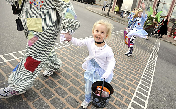 Dressed as &quotCinderella&quot, four-year-old Alyssa Griffin of Washington, ME holds onto her mom Cristie Griffin (cq) as they parade across Main Street to Bangor's Pickering Square  as part of Bangor's Halloween Downtown Block Party Saturday afternoon. Directly behind them is Alyssa's cousin Libby Matson of Old Town who was dressed at Alice of &quotAlice in Wonderland&quot (Bangor Daily News/John Clarke Russ)