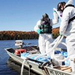 PHOTO CREDIT: MDIF&W Public Relations Rep Travis Barrett; BRP 7: Maine Department of Inland Fisheries and Wildlife biologists, who became licensed pesticide applicators, prepare pumps and hoses for infusion of liquid rotenone into the deep water pond.