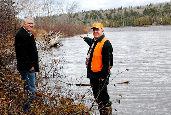 Retired Game Warden Jim Dumond (right) points to a spit of land in  