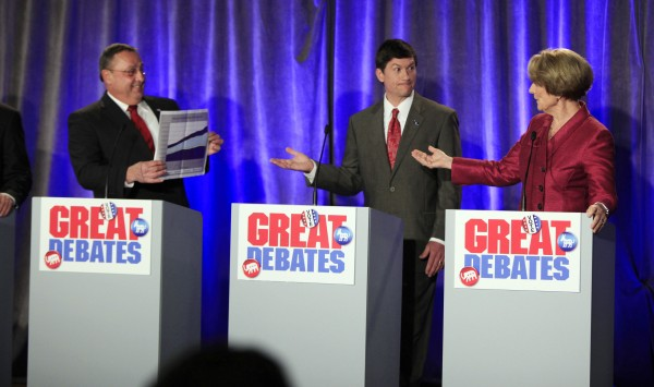 Republican gubernatorial candidate Paul LePage, left, holds up a chart while debating the state budget with Democratic candidate Elizabeth Mitchell, right, while independent candidate Kevin Scott, center, gets caught in the middle on Saturday during a debate in Portland.