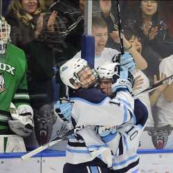 Maine's Spencer Abbott (13) and Brian Flynn (10) celebrate their third-period goal in front of the North Dakota bench and goalie Brad Eidsness (31) in Orono, Saturday, Oct. 23, 2010.