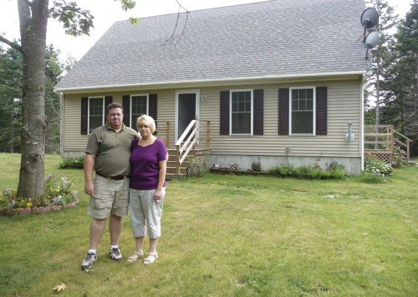 Brent and Beth Hartford stand in front of what they called their dream home in Milbridge, Maine. The Hartfords are being sued by the home's distributors, North East Homes of Ellsworth, for the cost of the home, while the Hartfords have countersued, saying the home was constructed incorrectly, allowing mold to bloom. Brent Hartford said the home is making his family sick and is asking for reparations.