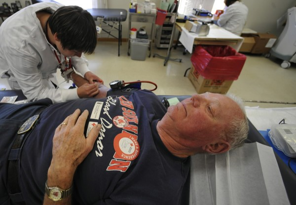 Becky Saulnier, a team supervisor at the Bangor Donor Center for the American Red Cross, marks an arm vein of donor Donald Wiswell of Orrington before drawing his blood at the center August 24, 2010.
