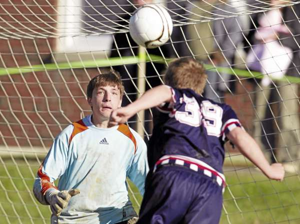Jay Bishop of Bangor Christian heads the ball on goal during first half action at the Eastern Maine Class D boys soccer championship held in Bangor on Nov., 2010. Calvary Chapel goaltender Devon Warman made the save. (Photo by Monty J. Rand)