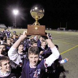 Bradley Wilcox (left) and Ben Groski (holding the trophy) lead the Bangor Christian team's victory parade past the stands after defeating Richmond High School 5-2 in the Class D  boys state soccer championship in Hampden Saturday night. (Bangor Daily News/John Clarke Russ)