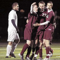 Bangor's Luke Hetterman (5), Phil Frost (23), and Seth Freudenberger (20) celebrate a goal as Portland's Brett O'Kelly walks past in the first half of the Class A state final in Falmouth, Saturday, Nov. 6, 2010. Bangor won 3-2. Bangor Daily News/Michael C. York