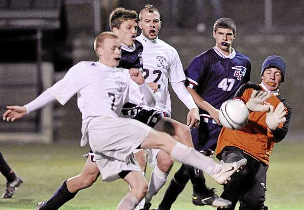 Bangor Christian goalkeeper Tyler Alexander, right,  blocks a goal attempt from Richmond's Peter Lorbeski (7) as Bangor Christian's Ben Groski (second from left), RIchmond's Kyle O'Brien (22) and Bangor Christian's Matthew Swanson (47) converge during the boys Class D state soccer championship in Hampden Saturday night. Bangor Christian defeated Richmond 5-2. (Bangor Daily News/John Clarke Russ)