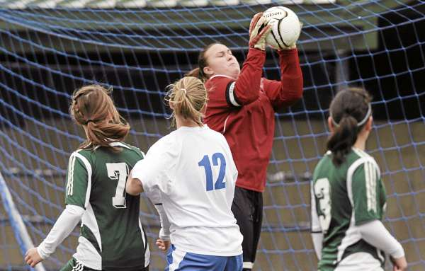 Fort Kent goalkeeper Carissa Pelletier makes a save on a Sacopee Valley player as teammates Alexis Desjardins (7), Michela Desjardins (right) and Sacopee's Amanda Cressey (12) look on during Saturday's Class C girls soccer state title game in Hampden. The Hawks edged the Warriors 2-1 in overtime.