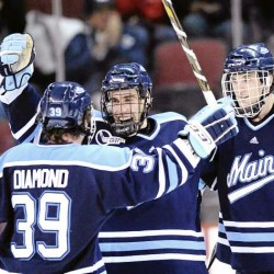 Jeff Dimmen (center) celebrates his unassisted goal at 6:12 of the third period with teammates Joey Diamond (39) and Robby Dee during Saturday night's Hockey East game against Boston University in Boston. The teams battled to a 2-2 overtime tie.