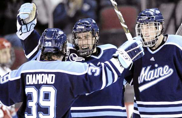 Jeff Dimmen (center) celebrates his unassisted third-period goal with teammates Joey Diamond and Robby Dee against Boston University in Boston Saturday night. Maine tied BU 2-2 and is now 4-1-3. After two successive weekends with just one game, Maine will have four two-game weekends leading up to the Christmas break with a weekend off in between. PHOTO BY STEVE MCLAUGHLIN