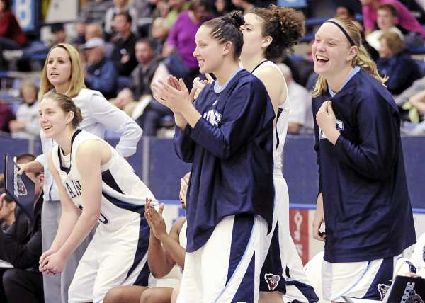 University of Maine women's basketball assistant coach Caren Fiorillo (left) and players Amber Smith, Tanna Ross, Gabrielle Babbe (partially obscured) and Jaymie Druding applaud during a recent exhibition game against Husson. Coach Cindy Blodgett's Black Bears seek considerable improvement this season. (BDN Photo by Michael C. York)