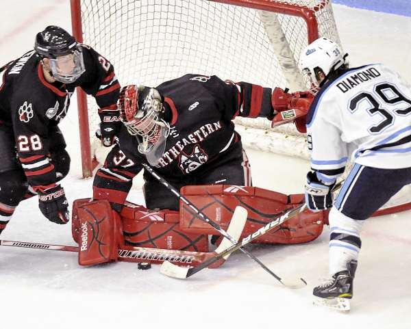 Northeastern goalie Chris Rawlings (37) and defenseman Mike Hewin (28) try to keep a loose puck away from Maine's Joey Diamond (39) in the first period of their game in Orono, Friday, Nov. 12, 2010. Maine won 4-2. Bangor Daily News/Michael C. York
