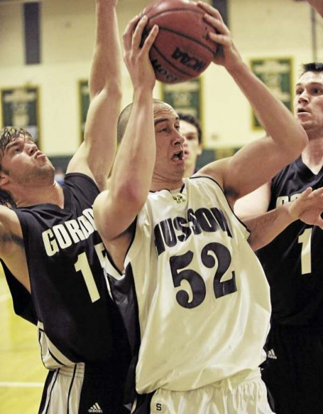 Husson University's Marc Zaharchuk (52) grabs a rebound as Gordon College's Austin Bentson, left, and Greg Walk pressure in the first period of their game at Newman Gym Tuesday night. (Bangor Daily News/John Clarke Russ)