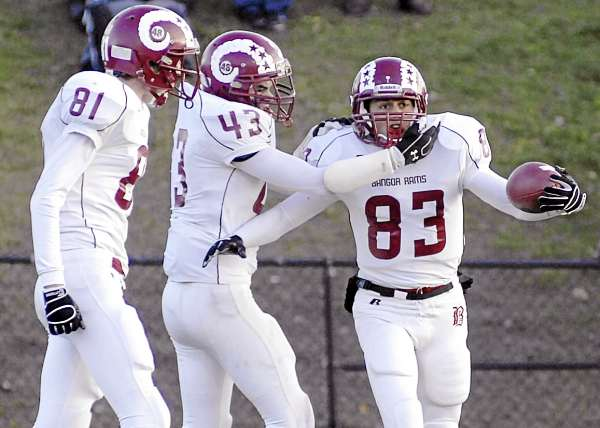 Bangor's Nick Sherwood (83) is congratulated by teammates Nic Cota (43) and Sean Mackintosh (81) after a touchdown  in the first half of their Class A state football championship game against Cheverus in Portland Saturday. The Stags of Portland won 46-8.