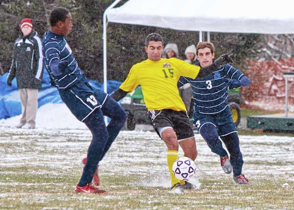 Amine El Moumen (center) of the University of Maine-Fort Kent splits St. Thomas (Fla.) defenders Michalson Platon (left) and Marco Generari during Saturday's NAIA men's soccer tournament opening-round game in Fort Kent. El Moumen scored a goal as the Bengals pulled out a 3-2 victory.