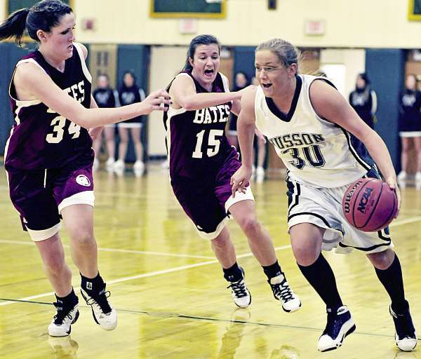 Husson's Kelli Murray (30) drives up the floor under pressure from Bates' Jessie Igoe (34) and Kelsey Flaherty (15) in the first half of their game Monday at Husson's Newman Gym in Bangor. Bates won 84-79.