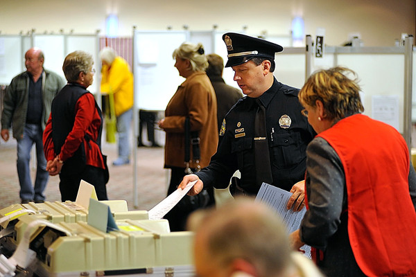 Bangor police officer Jim Dearing casts his ballot at Bangor Civic Center Tuesday afternoon, four days after being denied access to a polling booth to fill out an absentee ballot. On Friday, Officer Dearing would not comply with an election warden's request to relinquish his service firearm while voting. Dearing was on duty at the polls during the day and voted near the end of his shift.(Bangor Daily News/John Clarke Russ)