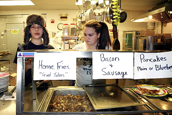 Wearing a hat warm enough for Alaska, Brooksville Elementary School student Aidan Byrne, works with classmate  Jasmine McDonald at an earlier breakfast to raise funds for their class's trip to Alaska where they will watch the start of the annual Iditarod sled dog race. The seventh and eighth graders will hold a 5k race and another breakfast this weekend to continue their fundraising efforts. Photo courtesy of Nada Lepper. w/Hewitt story