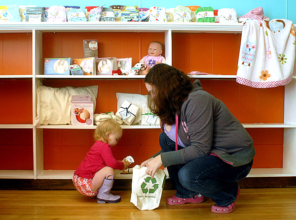 BANGOR, ME -- OCTOBER 13, 2010 --Beth Lundy and her daughter Zoe, 18 months, put items on shelves at Central Street Farmhouse, a new business coming to downtown Bangor which will feature home brewing, cheese making and wine on the first floor and a baby boutique on the second floor focusing on cloth diapers, nursing and carriers.   LINDA COAN O'KRESIK