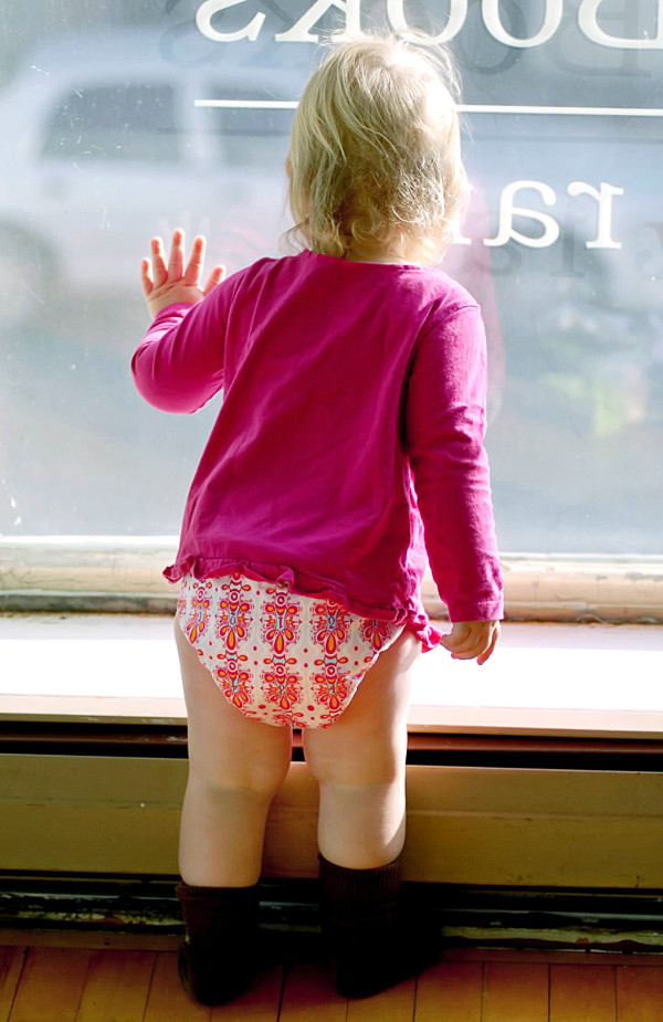BANGOR, ME -- OCTOBER 13, 2010 -- Zoe Lundy, 18 months, watches traffic go by from the second floor of Central Street Farmhouse in downtown Bangor. The new business will have home brewing, cheese making and wine on the first floor and a baby boutique on the second floor focusing on  cloth diapers, nursing and carriers. Zoe is wearing a Rump-a-rooz diaper, which is one of several brands the Lundy's will carry in their store.   LINDA COAN O'KRESIK