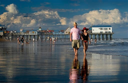 FILE - In this Aug. 26, 2010 file photo, Dan Horner, left, and Cynthia Belaskie, of Toronto, stroll along the ocean in Old Orchard Beach, Maine. October marked a milestone of 12 straight months of warmer-than-usual temperatures in Maine. While the Northeast as a whole has been warm this year, no other state has had a streak like Maine's. (AP Photo/Robert F. Bukaty, File)