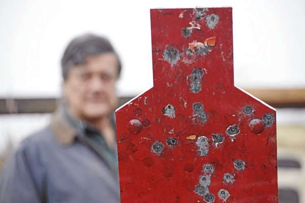 (BANGOR DAILY NEWS PHOTO BY JOHN CLARKE RUSS)  CAPTION  Urey W. Patrick stands behind a metal silhouette he uses as a target in his backyard practice range in WInterport. Patrick is a retired F.B.I. special agent who has been teaching police for more than 25 years how to use deadly force properly. (Bangor Daily News/John Clarke Russ)