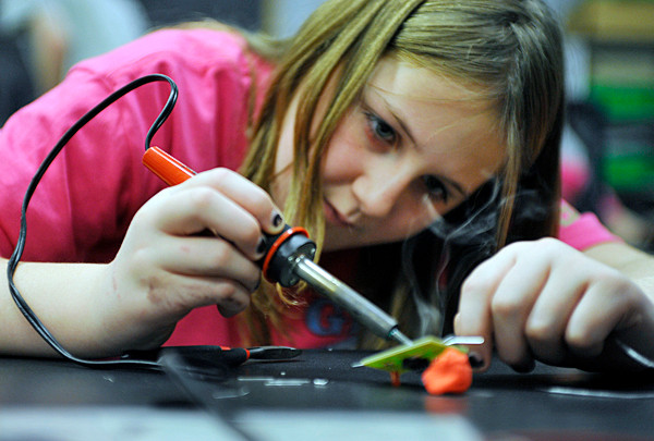 Rebecca Peterson, 11, of Girl Scout Troop 816 in Ellsworth solders the lead to a circuit board to power a light emitting diode while participating in Saturday's engineering education event at the University of Maine in Orono. A large group of Girl Scouts and their leaders from across the state came to U Maine to  take part in Transforming Leadership: Engineering for their Future. (Bangor Daily News/John Clarke Russ)