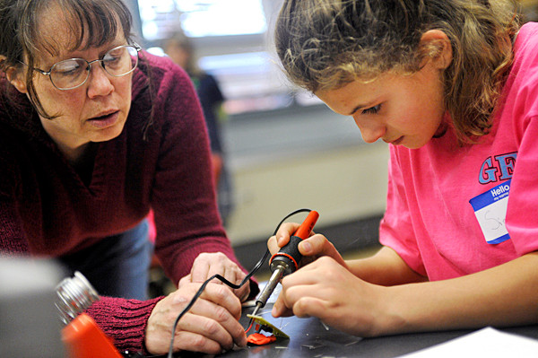 Rosemary Smith, a professor of engineering, helps Sierra Kay of Girl Scout Troop 3063 in Augusta solder the lead to a circuit board to power a light emitting diode while participating in Saturday's engineering education event at the University of Maine in Orono. A large group of Girl Scouts and their leaders from across the state came to U Maine to  take part in Transforming Leadership: Engineering for their Future. (Bangor Daily News/John Clarke Russ)