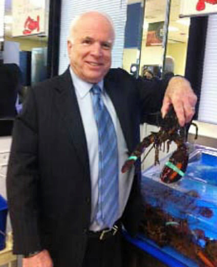 Sen. John McCain poses with a lobster at Bangor International Airport in Bangor on Friday night.    Two flights bound for Nova Scotia on Friday afternoon were diverted by bad weather to Bangor Inter-national Airport, resulting in six U.S. senators and U.S. Homeland Security Secretary Janet Napoli-tano spending the night in Bangor. The VIPs joined Sen. Susan Collins and the Maine Troop Greeters in welcoming two flights of military personnel that stopped over at the airport Friday night. Pictured (left to right) are: Troop Greeter Bill Knight; Sen. Jeff Sessions of Alabama; Sen. Lindsey Graham of South Carolina; Secretary Janet Napolitano; an unidentified troop greeter; Sen. Barbara Mikulski of Maryland; another unidentified troop greeter; Sen. Jeanne Sha-heen of New Hampshire; two more unidentified troop greeters; Sen. Susan Collins of Maine; Sen. John McCain of Arizona; and Sen. Mark Udall of Colorado.