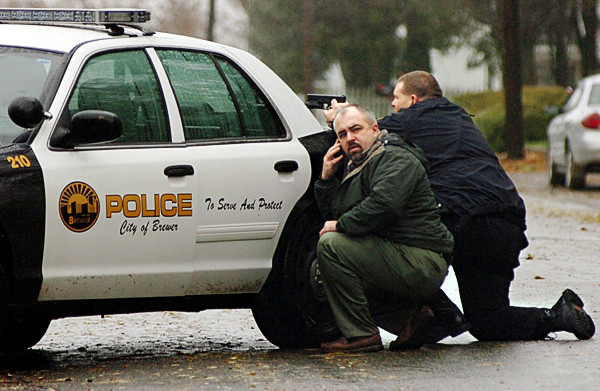 Brewer Police officer  Raymond Gotreau, right , with gun drawn,  and Brewer Police Capt. Jason Moffitt (on cell phone) crouched behind a patrol car as they helped secure an area around a house on 10 Blake St. in Brewer Monday afternoon, Nov. 8, 2010. Police removed a man from the home and took him into custody. They restricted traffic on Blake Street for more than a half hour. (Bangor Daily News/John Clarke Russ)