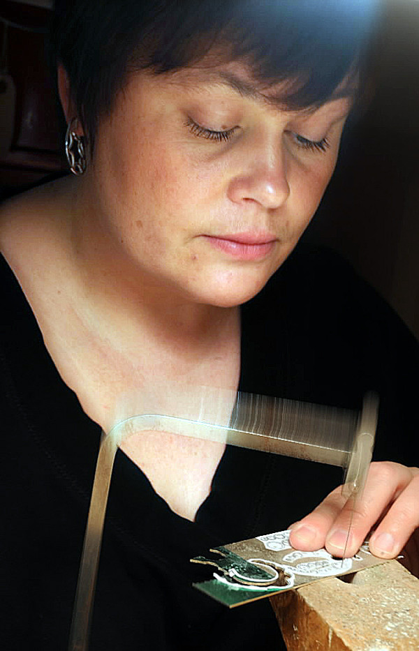 Jewlery artist Jen Lisa uses patterns to cut 18-gauge sterling silver which will be made into earrings at her home workshop in South China on Wednesday, October 27, 2010. (Bangor Daily News/Kevin Bennett)