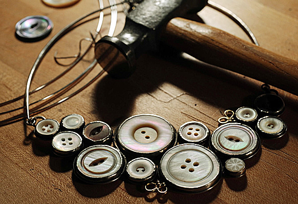 A finished necklace by Jen Lisa of South China sits on her work bench on Wednesday, October 27, 2010. Lisa says she buys iridescent buttons online or looks for them at yard sales and has even had older women donate them from their button collections. (Bangor Daily News/Kevin Bennett)